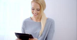 Jeune femme heureuse occupée avec la tablette clips vidéos