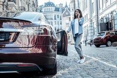 Jeune femme heureuse ouvrant sa portière de voiture Images stock