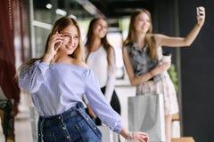 Jeune femme heureuse parlant au téléphone dans le centre commercial Photos libres de droits