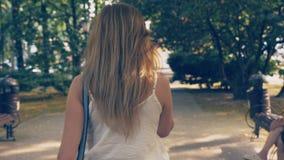 Jeune femme heureuse parlant au téléphone, marchant le long du bord de mer un jour ensoleillé chaud d'été 4k, mouvement lent clips vidéos