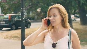 Jeune femme heureuse parlant au téléphone, marchant le long du bord de mer un jour ensoleillé chaud d'été 4k, mouvement lent banque de vidéos