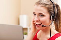 Jeune femme heureuse parlant sur son ordinateur portable photos stock