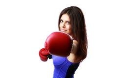 Jeune femme heureuse poinçonnant in camera avec le gant de boxe Photographie stock