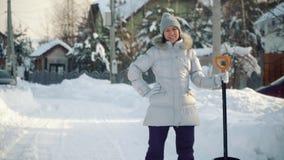 Jeune femme heureuse posant à l'appareil-photo avec la pelle dans les banlieues en hiver banque de vidéos