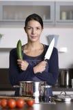 Jeune femme heureuse posant dans sa cuisine photographie stock libre de droits