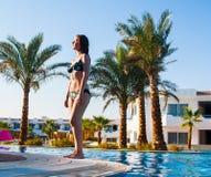 Jeune femme heureuse posant en maillot de bain de bikini au-dessus de piscine et plage avec le fond de palmiers Photos stock