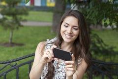 Jeune femme heureuse prenant des photos à votre téléphone Images stock