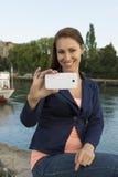 Jeune femme heureuse prenant des photos avec le téléphone intelligent Photo libre de droits
