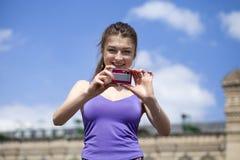 Jeune femme heureuse prenant des photos sur votre appareil-photo Images stock