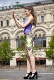 Jeune femme heureuse prenant des photos sur votre appareil-photo Photos stock