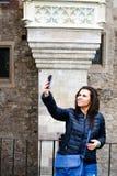 Jeune femme heureuse prenant un selfie au château de Corvin, Roumanie Photos stock