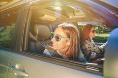 Jeune femme heureuse regardant en arrière par la fenêtre Photo stock