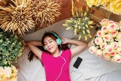 Jeune femme heureuse s'étendant sur le plancher en musique de écoute par l'intermédiaire de Sma photo stock