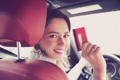 Jeune femme heureuse s'asseyant à l'intérieur de sa nouvelle voiture montrant la carte de crédit photo stock