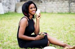 Jeune femme heureuse s'asseyant au parc image stock