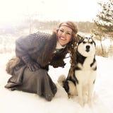 Jeune femme heureuse s'asseyant avec le chien de chien de traîneau sibérien Images libres de droits