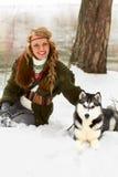 Jeune femme heureuse s'asseyant avec le chien de chien de traîneau sibérien Images stock