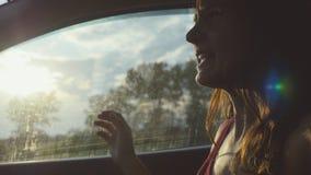 Jeune femme heureuse s'asseyant dans le passager de voiture regardant la fenêtre le jour ensoleillé appréciant le tour rural de v Image libre de droits