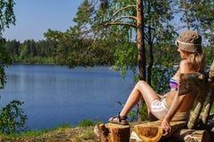 Jeune femme heureuse s'asseyant dehors sur le banc devant un lac avec le seaview photo stock