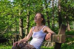 Jeune femme heureuse s'asseyant dehors sur le banc et détendant avec les yeux étroits photographie stock libre de droits