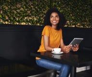 Jeune femme heureuse s'asseyant en café tenant le comprimé numérique image libre de droits