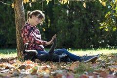 Jeune femme heureuse s'asseyant sous un arbre en parc jouant avec He Image stock