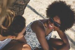 Jeune femme heureuse s'asseyant sur la plage avec rire d'ami Image stock