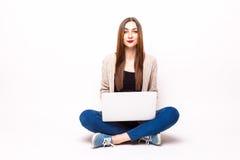 Jeune femme heureuse s'asseyant sur le plancher avec les jambes croisées et employant le lapto images stock