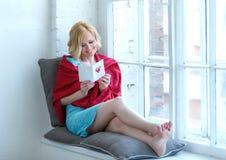 Jeune femme heureuse s'asseyant sur le rebord de fenêtre avec la carte postale d'amour Images libres de droits