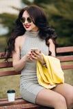 Jeune femme heureuse s'asseyant sur le sofa en tissus confortables avec la tasse de café Veste jaune lumineuse de mode, robe gris Photos stock