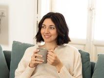 Jeune femme heureuse s'asseyant sur le sofa ? la maison avec une boisson chaude Dans le concept de loisirs et de temps disponible photographie stock