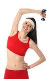 Jeune femme heureuse s'exerçant avec un haltère Photographie stock