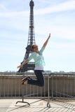 Jeune femme heureuse sautant contre Tour Eiffel Photographie stock libre de droits
