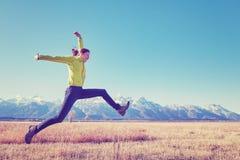 Jeune femme heureuse sautant sur un pré de montagne Photo stock