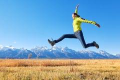 Jeune femme heureuse sautant sur un pré de montagne Photographie stock libre de droits