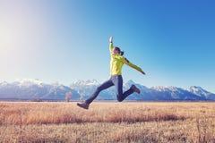 Jeune femme heureuse sautant sur un pré de montagne au coucher du soleil Image libre de droits