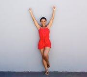 Jeune femme heureuse se penchant contre le mur gris avec des bras augmentés Photographie stock libre de droits