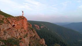 Jeune femme heureuse se tenant au bord d'une falaise images stock