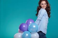 Jeune femme heureuse se tenant au-dessus du mur bleu et tenant des ballons image libre de droits