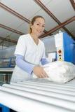 Jeune femme heureuse se tenant aux nettoyeurs à sec photo libre de droits