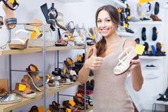 Jeune femme heureuse se tenant avec la chaussure choisie Images stock