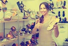 Jeune femme heureuse se tenant avec la chaussure choisie Photo stock