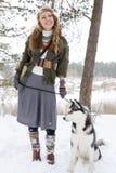 Jeune femme heureuse se tenant avec le chien de chien de traîneau sibérien Photographie stock libre de droits