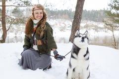 Jeune femme heureuse se tenant avec le chien de chien de traîneau sibérien Image libre de droits