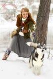 Jeune femme heureuse se tenant avec le chien de chien de traîneau sibérien Photos stock