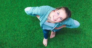 Jeune femme heureuse se tenant dans l'herbe verte photos stock