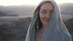 Jeune femme heureuse se tenant en vent contre un paysage de coucher du soleil de désert avec une belle fusée du soleil banque de vidéos