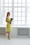 Jeune femme heureuse souriant avec le groupe de tulipe dans la robe jaune Images stock