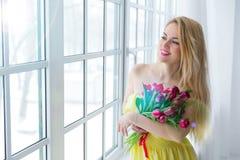 Jeune femme heureuse souriant avec le groupe de tulipe dans la robe jaune 8 mars le jour des femmes internationales Images stock
