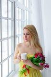 Jeune femme heureuse souriant avec le groupe de tulipe et le thé de tasse 8 mars Photo libre de droits